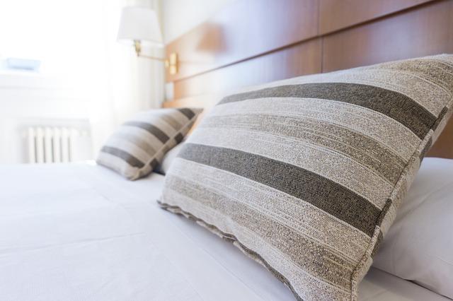 šedé polštáře na posteli