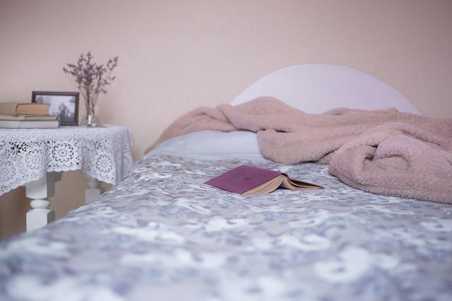 postel s růžovou dekou