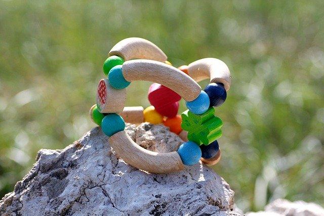 dřevěná hračka položená na kameni venku v přírodě
