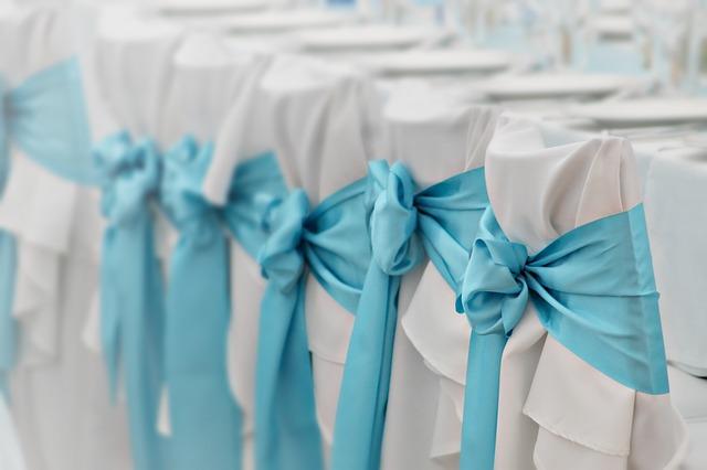 židle na svatbu s bílými potahy a modrými mašlemi, v pozadí bílý stůl