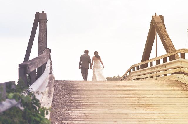 manželé jdou po dřevěném mostě, jsou na odchodu v dáli a obráceni zády