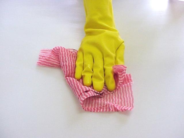ruka ve žluté rukavici čistící bílý povrch